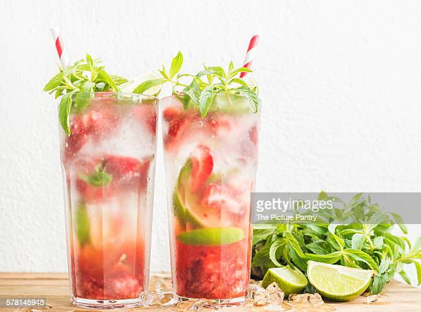 Strawberry mojito summer cocktails with mint and lime in tall glasses