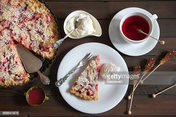 Strawberry rhubarb tart with whipped cream and cup of fruit tea