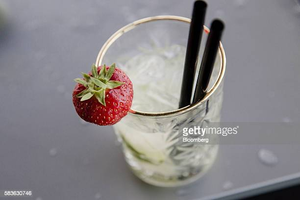 A strawberry sits on the rim of a caipirinha cocktail glass in the guest lounge bar on board Hotel OFF Paris Seine in Paris France on Wednesday July...