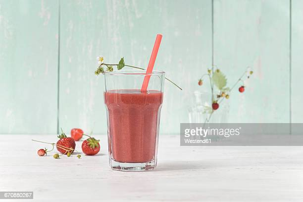 Strawberry smoothie in glass with drinking straw