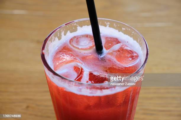 strawberry soft drink with ice, in a glass glass on a wooden table in a street cafe or restaurant. - 西シベリア ストックフォトと画像
