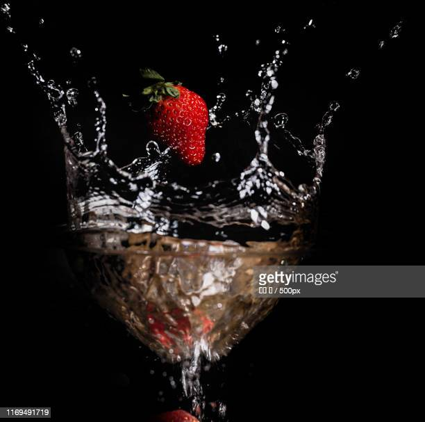Strawberry splashing in water against black background
