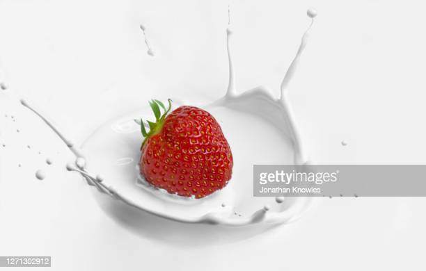 strawberry splashing in yogurt - falling stock pictures, royalty-free photos & images