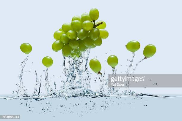 strawberrys jump out  on line except one  from water - white grape stock photos and pictures