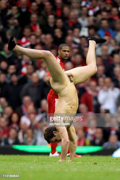 A streaker cartwheels across the pitch as Glen Johnson of Liverpool looks on during the Barclays Premier League match between Liverpool and Tottenham...