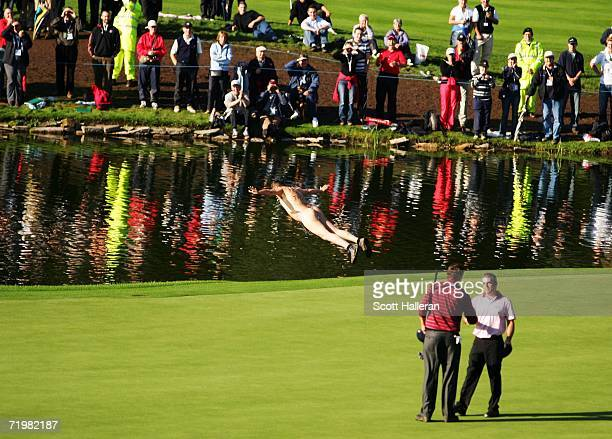 A streaker dives into the water by the 18th green as Paul McGinley of Europe shakes hands with JJ Henry of USA after they halved their match on the...