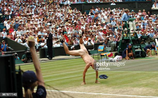 A streaker does a handstand interrupting Maria Sharapova of Russia during her quarterfinal match on Day 8 of the Wimbledon Championships July 4th 2006