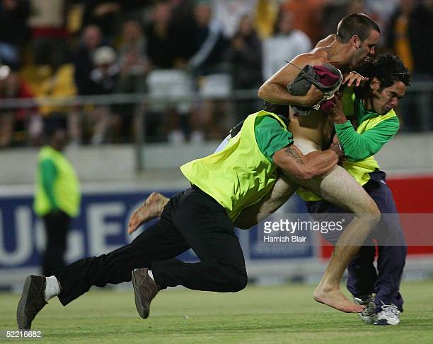 A streaker is brought down by two security guards during the 1st One Day International between New Zealand and Australia at Westpac Stadium on...