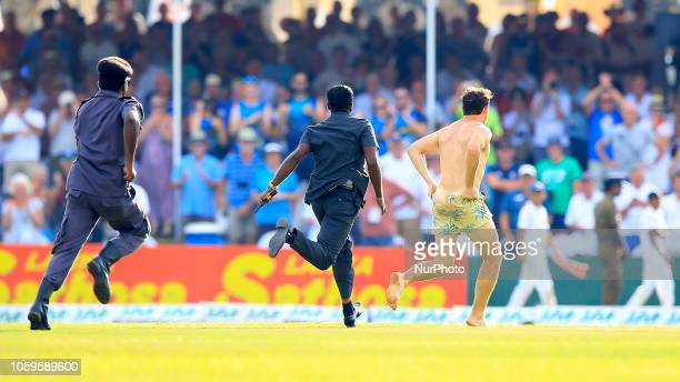 Streaker is chased away by security officers during the 4th day's play of the first test cricket match between Sri Lanka and England at Galle...