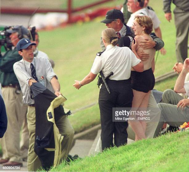 A streaker is covered up by a police officer