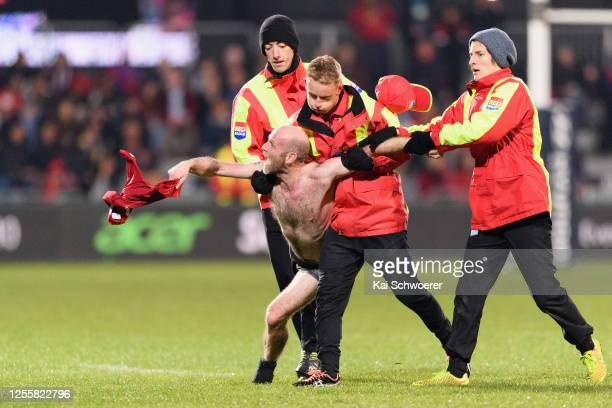 Streaker is escorted off the field by security during the round 5 Super Rugby Aotearoa match between the Crusaders and the Blues at Orangetheory...