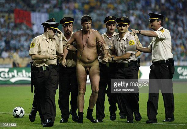 A streaker is led away by the police during the UEFA Cup Final match between Celtic and FC Porto held on May 21 2003 at the Estadio Olimpico in...