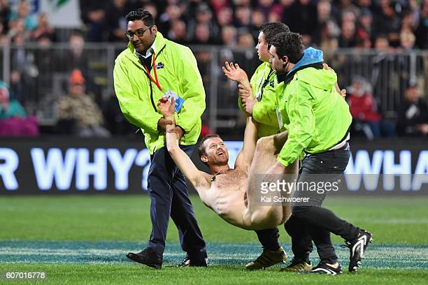 A streaker is led off the playing field by security staff during the Rugby Championship match between the New Zealand All Blacks and the South Africa...