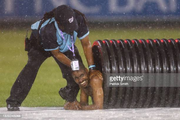 Streaker is pulled from the infield tarp roller by law enforcement and security during a rain delay between the Cincinnati Reds and against the...