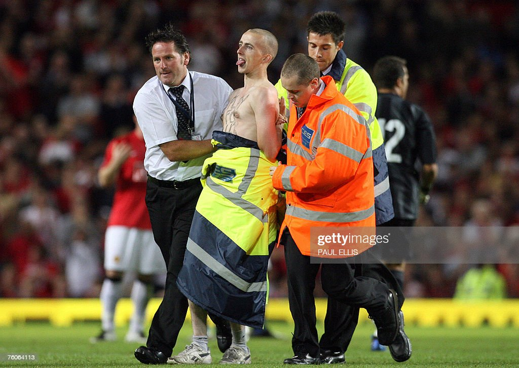 A streaker is removed from the pitch during the pre-season