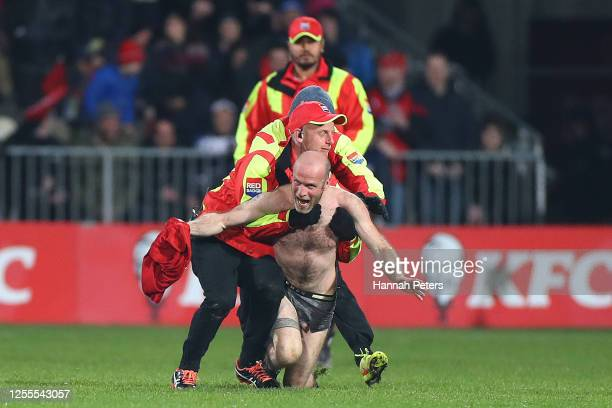 A streaker is stopped by security during the round 5 Super Rugby Aotearoa match between the Crusaders and the Blues at Orangetheory Stadium on July...