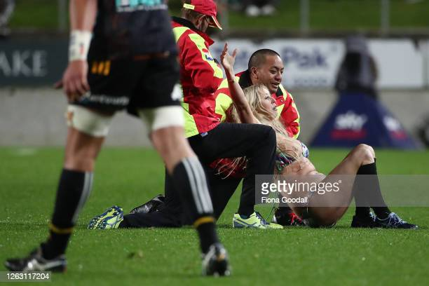 Streaker is tackled by security during the round eight Super Rugby Aotearoa match between the Chiefs and Crusaders at Waikato Stadium on August 01,...