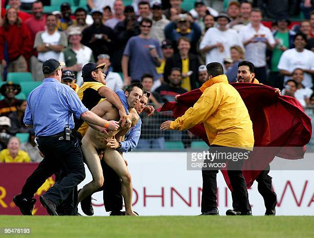 A streaker is tackled by security staff after running on the field during the Super Series Test match between Australia and the World XI in Sydney 15...