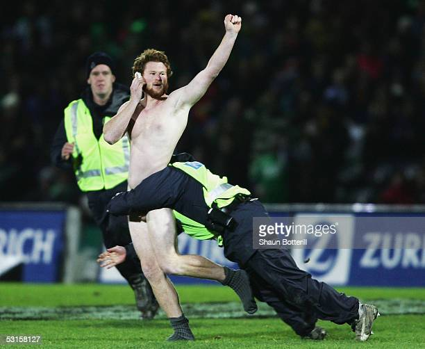 A streaker is tackled by the police during the match between British and Irish Lions and Manawatu at Arena Manawatu on June 28 2005 in Palmerston...
