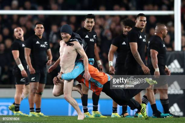 A streaker is tackled during the International Test match between the New Zealand All Blacks and France at Eden Park on June 9 2018 in Auckland New...