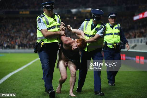 A streaker is taken away by police during the International Test match between the New Zealand All Blacks and France at Eden Park on June 9 2018 in...