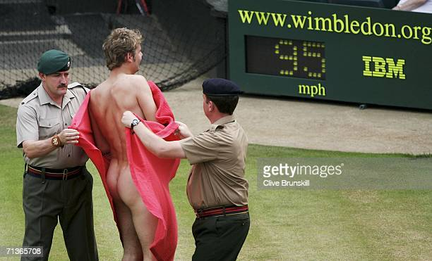 A streaker is taken off centre court by security after running across the court during the match between Maria Sharapova of Russia and Elena...