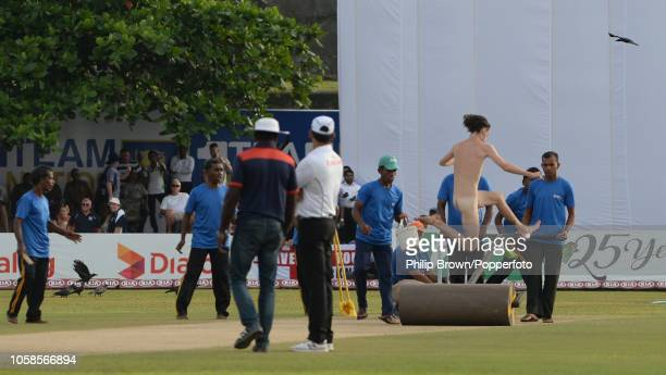 Streaker leaps over the roller at the change of innings during the 1st Cricket Test Match between Sri Lanka and England at the Galle Cricket Stadium...