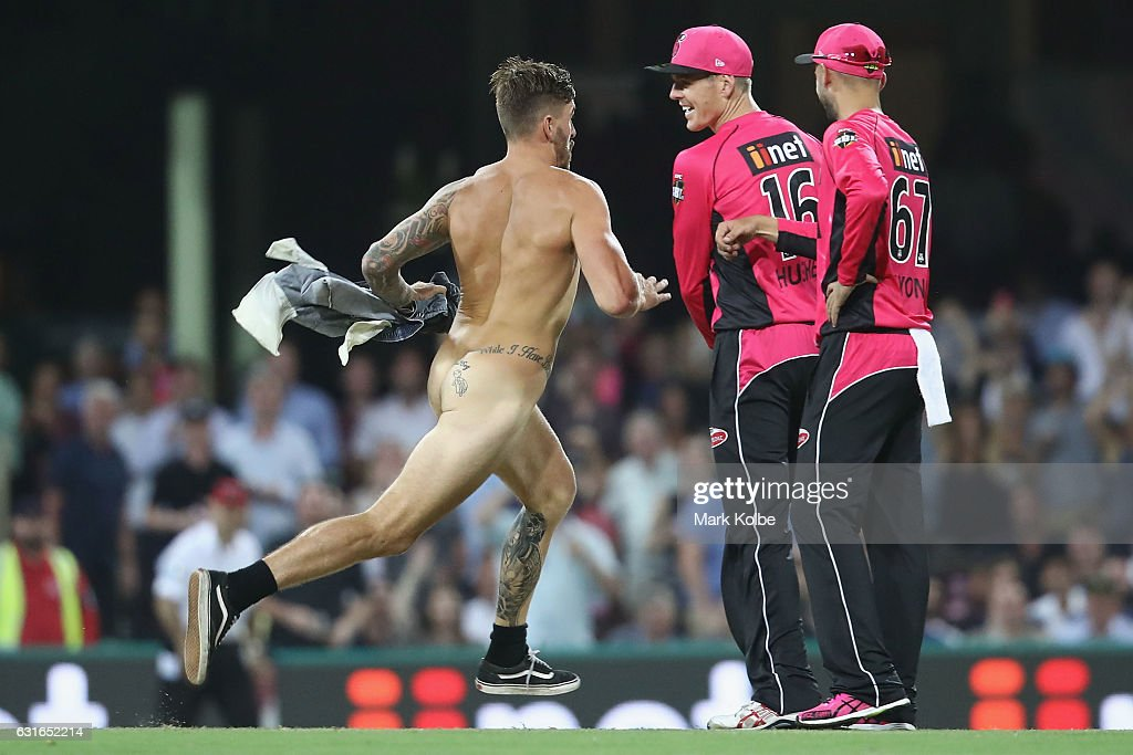 A streaker runs by Daniel Hughes and Nathan Lyon of the Sixers as he invades the pitch during the Big Bash League match between the Sydney Sixers and the Sydney Thunder at Sydney Cricket Ground on January 14, 2017 in Sydney, Australia.