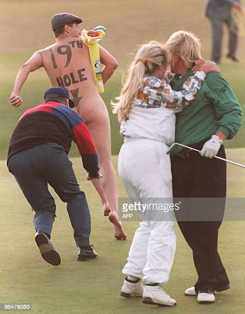 A streaker runs onto the 18th green as John Daly and his wife Paulette celebrate after Daly beat Costantino Rocca of Italy in a playoff to take the...