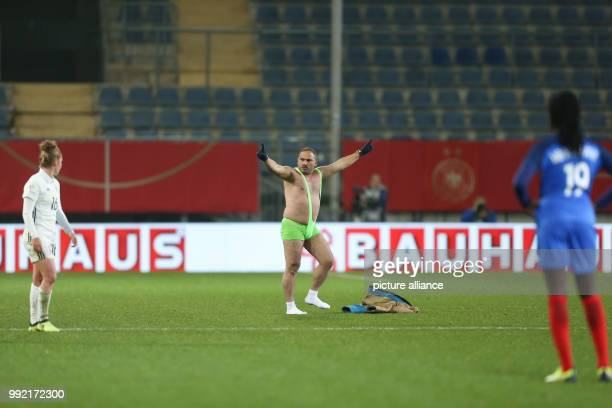 A streaker runs onto the field during the women's international friendly soccer match between Germany and France in the Schueco Arena stadium in...