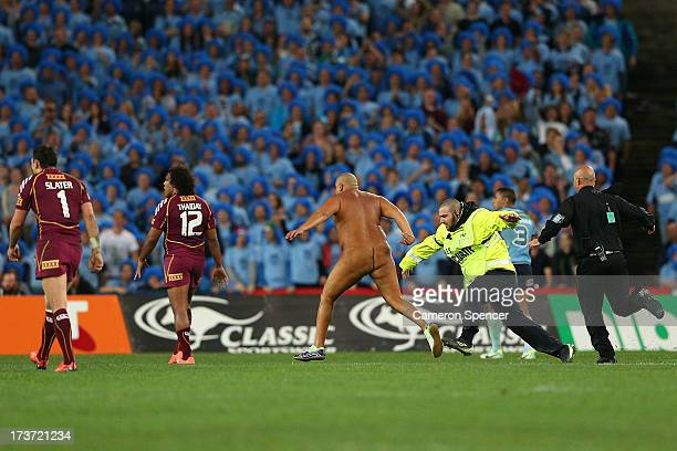 A streaker runs onto the field security guards during game three of the ARL State of Origin series between the New South Wales Blues and the...