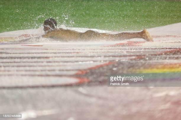 Streaker slides on the infield tarp during a rain delay between the Cincinnati Reds and against the Washington Nationals at Nationals Park on May 26,...