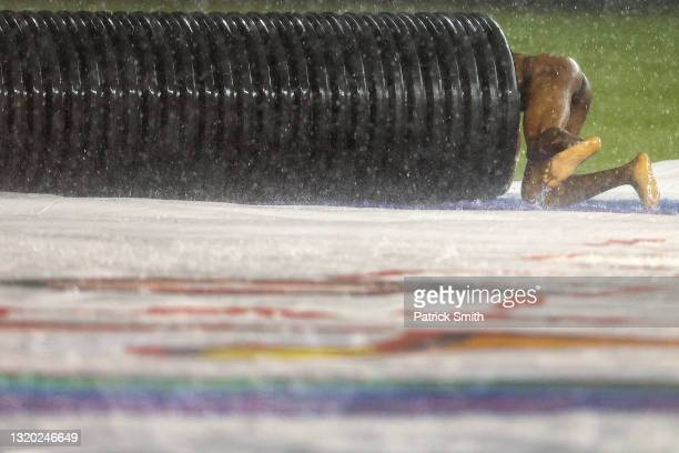 Streaker slides on the infield tarp into the tarp roller during a rain delay between the Cincinnati Reds and against the Washington Nationals at...