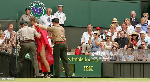A streaker surrounded by security men leaves the centre court as Maria Sharapova of Russia plays against compatriot Elena Dementieva in the...