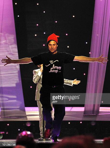 A streaker wearing a red cap and a tshirt reading Jimmy Jump appears on stage as Spain's Daniel Diges performs his song Algo Pequeñito during the...