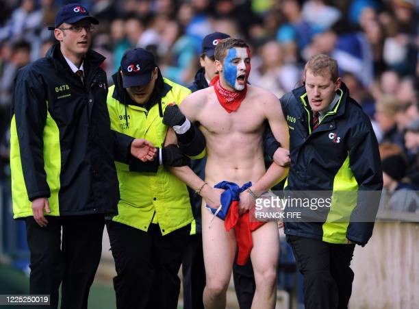 Streaker with his face painted in the French colours is evacuated from the pictch during the 6 Nations International rugby union match between...