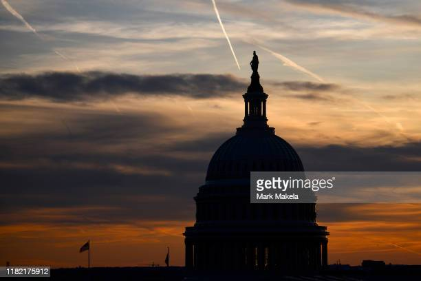 Streaks in the sky form at sunset behind the US Capitol Building on November 13 2019 in Washington DC In the first public impeachment hearings in...