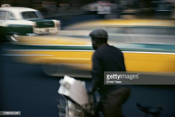 Streaks of green and yellow in a long exposure shot of a cyclist and passing traffic in New York City, 1957.