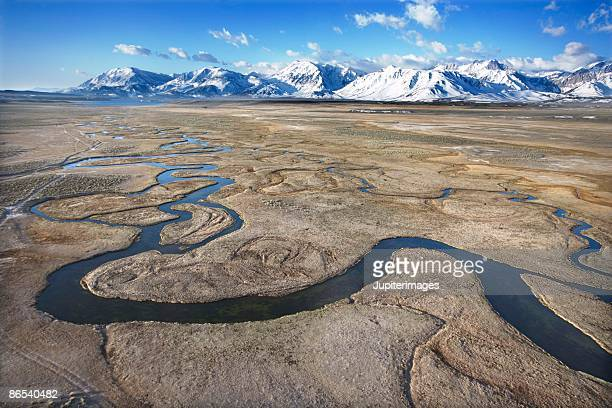 Stream in valley by snowy mountains