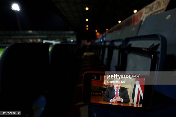 Stream of Boris Johnson's address to the nation is seen on a phone during the Carabao Cup Third Round match between Luton Town and Manchester United...
