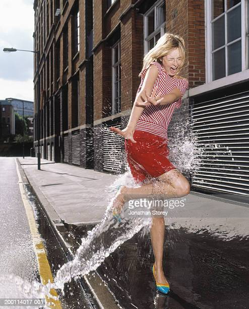 Stream of water hitting young woman on pavement