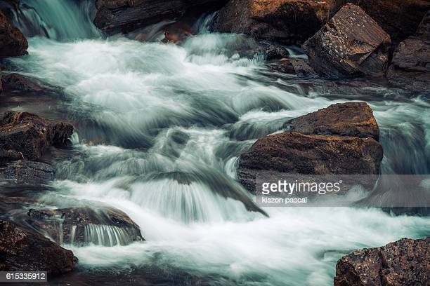 Stream water flowing through rocks in nature ( Sichuan , China )