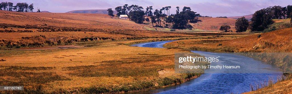 Stream winding through pasture land : Stock Photo