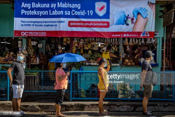Streamer showing information on COVID-19 vaccines is seen as Filipinos queue outside a wet market to stock up on food a day before a strict lockdown...