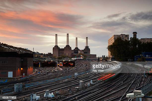 Streams of light worm their warm towards Battersea Power Station. It's sunrise and the colourful sky is a key feature in this railway landscape.