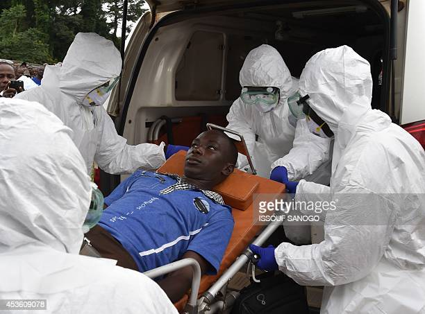 Strechers carry a man on a stretcher in an ambulance on August 14 2014 at the district hospital of Biankouma during a simulation operation organized...