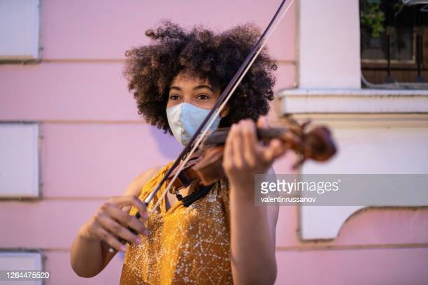 street afro musician playing violin and wearing protective face mask, during covid-19 - street artist stock pictures, royalty-free photos & images