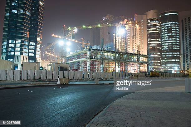 Street against illuminated construction site and buildings at night