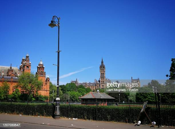 street amidst buildings against clear blue sky - glasgow stock pictures, royalty-free photos & images