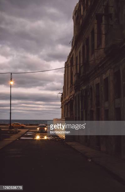 street amidst buildings against sky at dusk - bortes stock-fotos und bilder